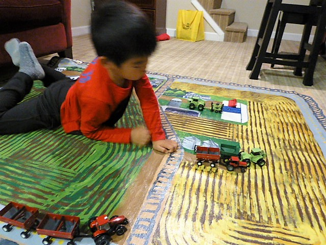 Grandson plays on another farm scene Lou painted.JPG