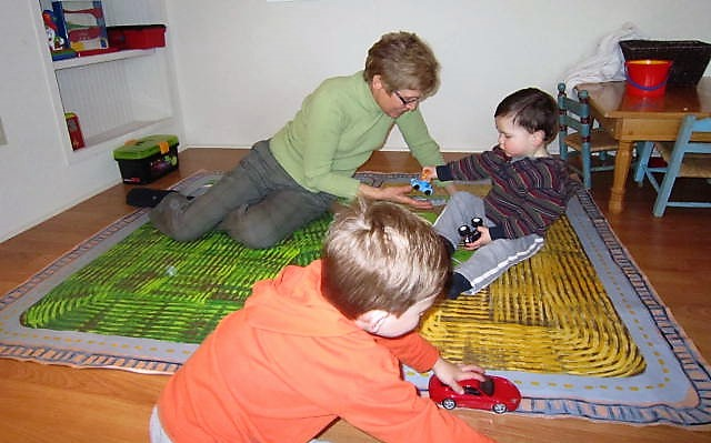 Lou with grandsons on floor cloth she painted like their farms.JPG