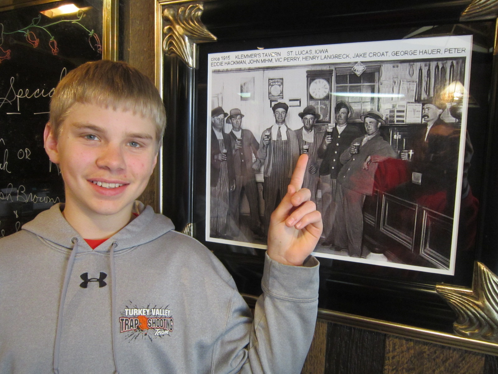 Cole Langreck points out great-great-grandfather in tavern photo.JPG