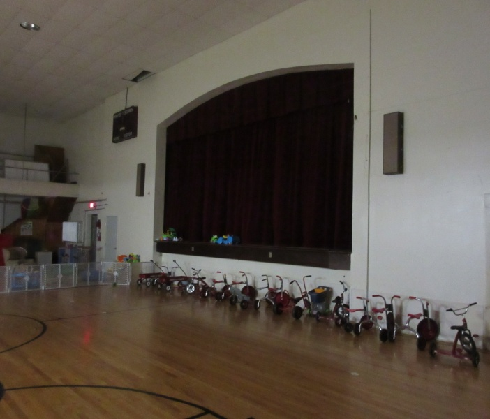 25 Daycare trikes and stage of old gym.JPG